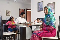 Arab Family of four dining while woman smiles