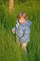 This cute blond haired Caucasian toddler 2 year old girl is wearing a blue coat while playing outdoors in the tall grass Vertical stock image, backgro...