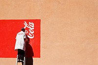 Man painting Coca Cola sign on restaurant wall, Morocco