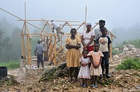 A family, victims of the earthquake in january 2010, next to their new earthquake-proof house with truss structure, which is made available by a Germa...