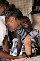 Young woman injured in the January 2010 earthquake receiving physiotherapist support from a relief organisation, Delmas 33 district, Port_au_Prince, H...