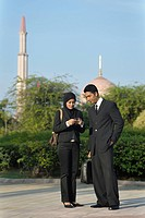 Businessman and woman using cell phone with mosque in the background