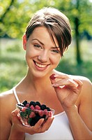 Woman eating raspberries and blackberries in the garden