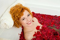 Young woman lying in bath with rose petals.