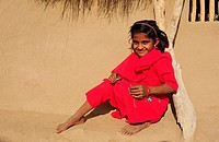 Little girl sitting in front of a traditional house, Thar Desert, Rajasthan, India, Asia