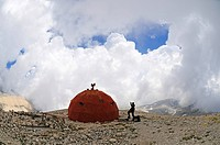 Mountaineer in front of a Bivouac shelter on the summit plateau of Monte Amaro, Caramanico Terme, Majella National Park, Abruzzo, Italy, Europe