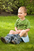 Boy sitting on a chamber pot in the garden
