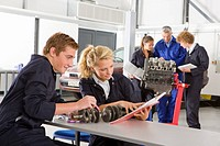 Students with auto part studying automotive trade in vocational school