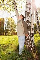 Little boy at birch tree in park