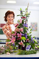 Smiling woman putting flowers into floral arrangement in classroom