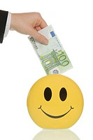 Business man putting a 100-euro note in a smiley piggy bank