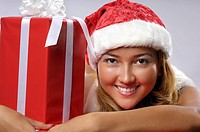 Portrait of a young smiling woman in Santa costume with a Christmas gift
