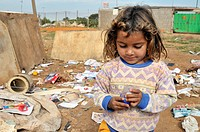 Girl, 8, playing with a toy she found at the informal dump outside her house, her family lives by collecting, separating and selling recyclable waste,...