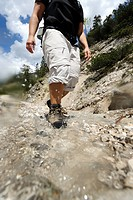 Woman crossing a mountain stream, ascent to Plumsjoch mountain, Karwendel mountain range, Tyrol, Austria, Europe