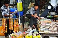 On the shopping street young boy is working