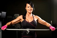 Asian woman working out on rower smiling