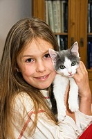 Young kitten, domestic cat in a girl´s arms, Germany