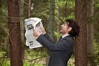 Young businessman with newspaper in a forest