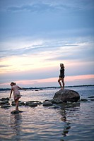Two girls playing on rocks in sea