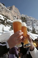 Two persons clinking wheat beer glasses, Alta Badia, Dolomites, Trentino_Alto Adige/Suedtirol, Italy