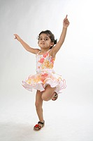 young girl of 4 years happy and jumping dancing lifting both hands upwards and one leg folded from knee MR 687D