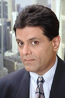 Executive looking at camera in office at top floors of skyscraper in modern city MR 687U