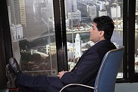 Executive relaxing in chair and looking out side of window in office at top floors of skyscraper in modern city MR 687U