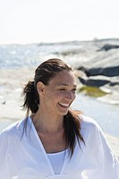 Woman standing and smiling in front of sea