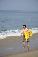 South Asian Indian young man holding yellow floating air bed in hand and walking on seashore , Shiroda , Dist Sindhudurga , Maharashtra , India MR 703...