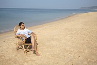South Asian Indian young lady taking sunbathe sitting on cane chair in sand at seashore , Shiroda , Dist Sindhudurga , Maharashtra , India MR703E