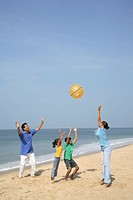 South Asian Indian parent and children playing with air filled plastic ball on seashore , Shiroda , Dist Sindhudurga, Maharashtra, India MR703D,703E,7...