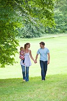 Mid adult couple walking through park, women carrying daughter