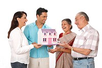 Young man and woman with old parent looking at dream house model MR703P,703Q,703R,703S