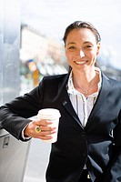 Portrait of cheerful businesswoman with takeaway coffee