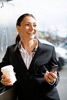 Cheerful businesswoman with takeaway coffee in one hand and mobile phone in another