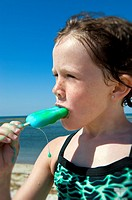 Girl eating a popcicle at the beach