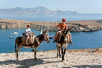 Two children riding donkeys, near Lindos, Rhodes, Dodecanese, Greece, Europe