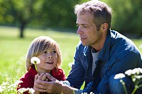 Father and son holding dandelion in bright sunlight