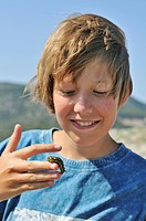 Boy, 13 years, with the caterpillar of a Spurge Hawk_moth Hyles euphorbiae on his hand, Croatia, Europe