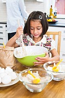 Girl baking in kitchen with mother in background