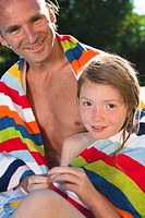 Father and daughter sitting at the edge of swimming pool