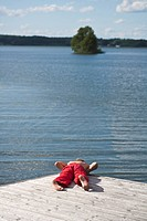 Boy lying on pier and looking at lake