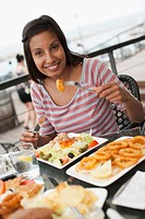 Portrait of woman eating meal at outdoor restaurant