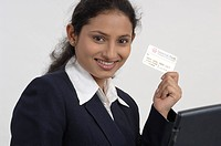 Office going South Asian Indian lady operating laptop showing Credit card MR_670V