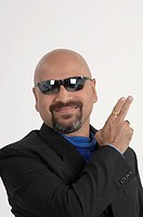 Portrait of South Asian Indian bald man wearing black goggles showing fingers gesture in right direction MR_ 670N