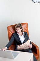 Business woman working on her laptop, holding a newspaper