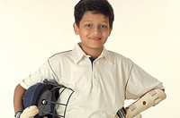 South Asian Indian boy wearing cricket costume holding helmet in hand MR 705_N