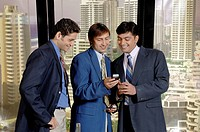 South Asian Indian businessmen standing and looking at mobile in his office MR 670D ,670E ,670F