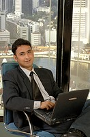 South Asian Indian businessman smiling sitting in office with laptop MR 670I