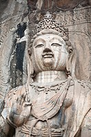Carved Buddhist statue, Fengxian Temple, Longmen Grottoes and Caves, Luoyang, Henan Province, China  Tang Dynasty